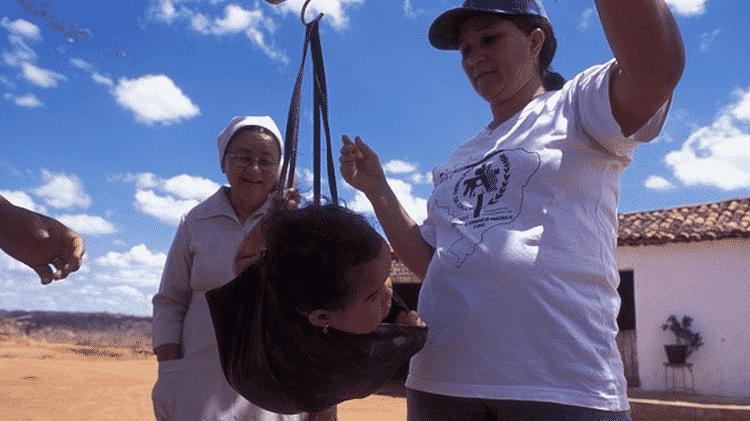 Prevalência de anemia por falta de ferro atingia 33% das crianças brasileiras mesmo antes da pandemia. Na foto, bebê é pesada por voluntárias da Pastoral da Criança - Getty Images - Getty Images