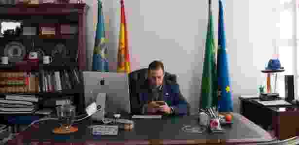 O prefeito Jose Antonio Rodriguez Salas trabalha no smartphone em seu escritório em Jun, na Espanha - Laura Leon/The New York Times