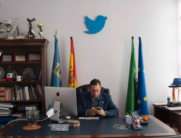 O prefeito Jose Antonio Rodriguez Salas trabalha no smartphone em seu escritório em Jun, na Espanha