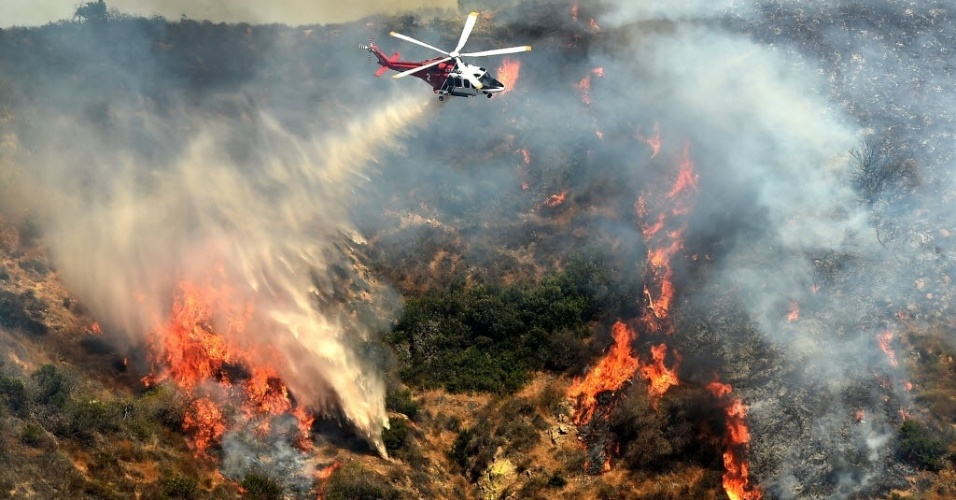 """19.jul.2016 - Mais de cem bombeiros trabalham para apagar um incêndio originado nesta terça-feira nas montanhas próximas ao famoso letreiro de Hollywood, em Los Angeles, informou o jornal """"Los Angeles Times"""". A fumaça pode ser vista a vários quilômetros de distância. As primeiras ligações de emergência foram registradas por volta das 15h locais (19h em Brasília), e o foco do incêndio se encontrava próximo à Route 101 no sentido norte, perto da Cahuenga Boulevard. Trata-se de um incêndio florestal causado por um problema no cabo elétrico da região e que ainda não ameaça nenhuma residência, informou Margaret Stewart, porta-voz do corpo de bombeiros de Los Angeles"""