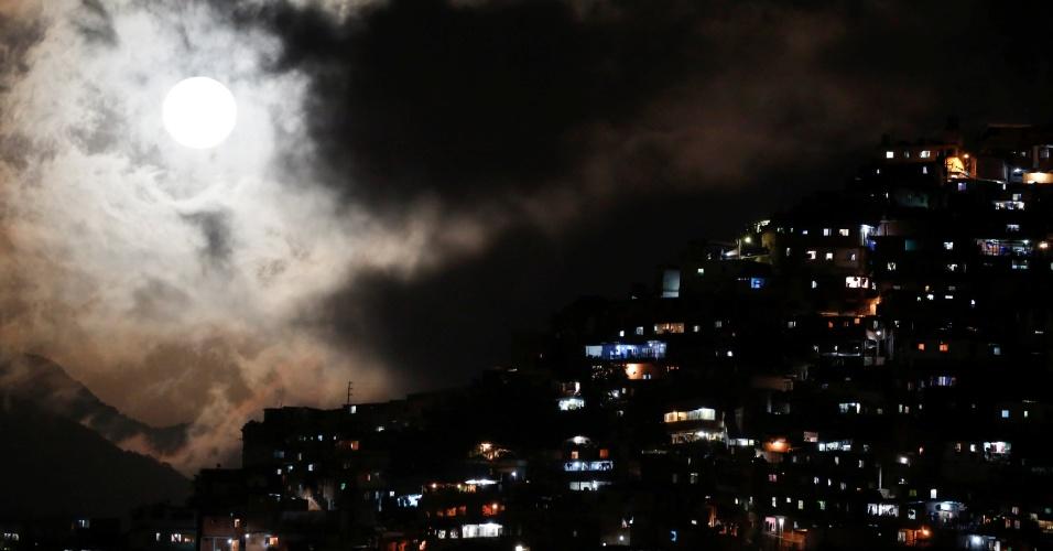 15.nov.2016 - Superlua é vista entre nuvens ao lado de favela em Caracas, na Venezuela