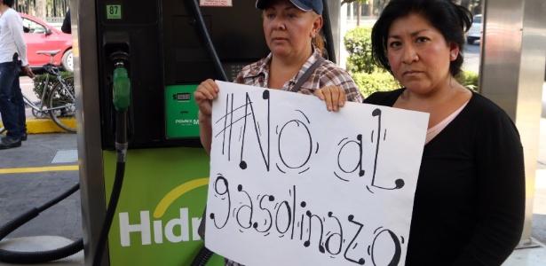 Mulheres protestam contra aumento do preço da gasolina em um posto