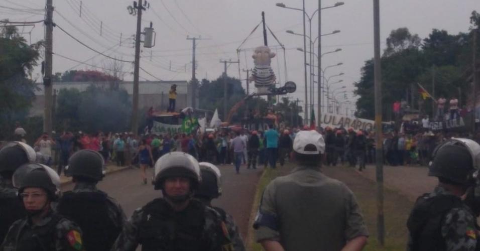 """22.mar.2018 - Policiais separam grupos opostos durante visita de Lula em Cruz Alta (RS). Ao fundo, manifestantes içam """"jaula"""" com pixuleco"""