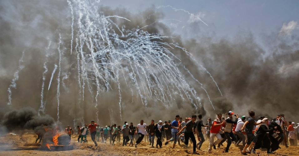 14.mai.2018 - Palestinos correm de bombas de gás durante protesto a leste de Jabalia, na fronteira da Faixa de Gaza com Israel