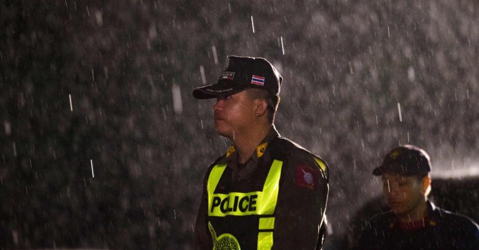 Policial tailandês monta guarda, sob chuva, em uma área próxima à caverna de Tham Luang, ao norte da Tailândia, onde 12 adolescentes e um adulto aguardam resgate há duas semanas
