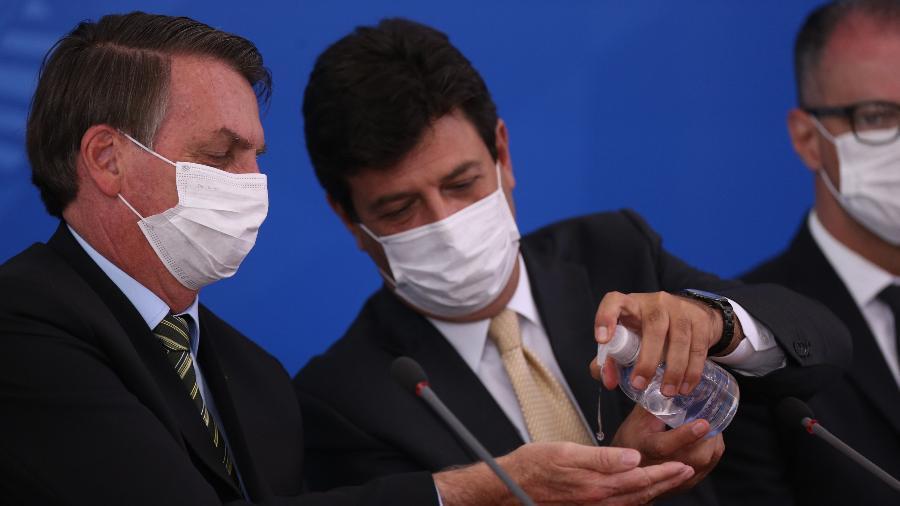 O ministro da Saúde, Luiz Henrique Mandetta, passa álcool gel nas mãos do presidente Jair Bolsonaro - Pedro Ladeira/Folhapres