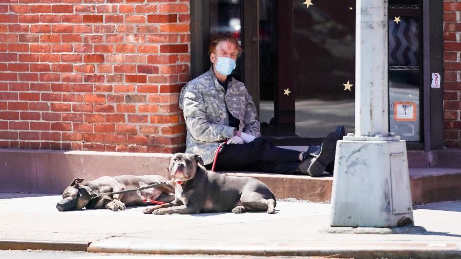 Homem com máscara de proteção contra coronavírus descansa na calçada durante passeio com os cães, em Nova York - Getty Images