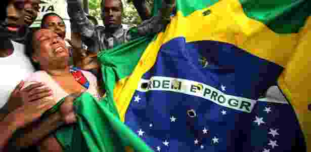 Mãe chora pela morte do filho, assassinado pela PM, em Costa Barros, na zona norte do Rio, em novembro de 2015 - Júlio César Guimarães/UOL