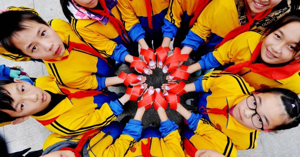 1°dez.2015 - Alunos seguram laços vermelhos para marcar o Dia Mundial de Luta contra Aids em Dexing, na província de Jiangxi, leste da China