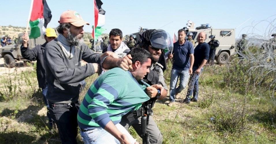 19.fev.2016 - Policial israelense agarra um manifestante palestino durante um protesto para marcar o 11º aniversário do ínicio das manifestações em Bilin, Ramallah, na Cisjordânia