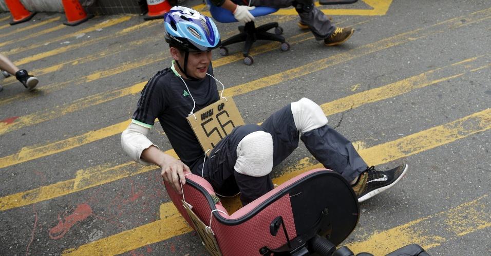 24.abr.2016 - Nessa corrida maluca, os tombos são inevitáveis. Na foto, o participante 56 cai enquanto tenta deslocar a cadeira de escritório durante o ISU-1 Grand Prix, em Tainan, sul de Taiwan, na China