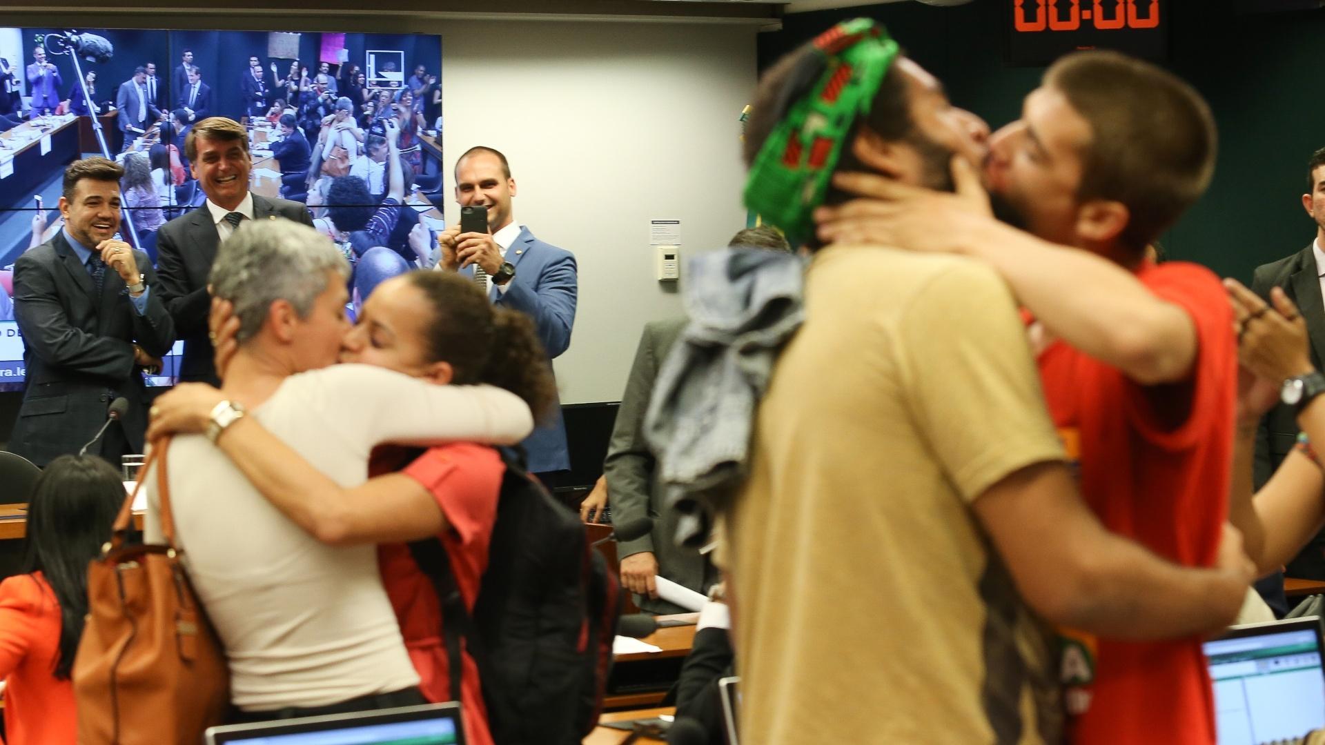 """24.mai.2016 - Os deputados federais Marco Feliciano (PSC-SP), Jair Bolsonaro (PSC-RJ) e Eduardo Bolsonaro (PSC-SP) observam """"beijaço"""" de participantes de audiência pública na Câmara sobre o Ministério da Cultura"""