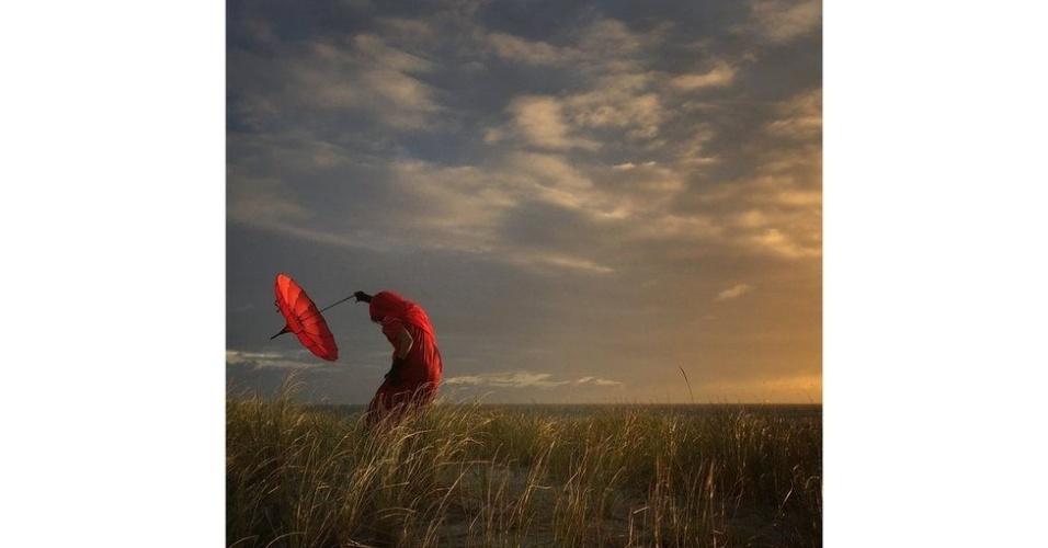 """""""Ela se dobra com o vento"""" é o título da fotografia do americano Robin Robertis, que ficou em segundo lugar no concurso. """"Estava em um curso para iPhone quando todos saímos para fotografar o entardecer"""", relata. """"Uma das coisas que sempre carrego quando viajo é este magnífico guarda-chuva vermelho. Enquanto outros registram fotos de paisagens bonitas, gosto de captar aspectos humanos dentro da cena"""""""