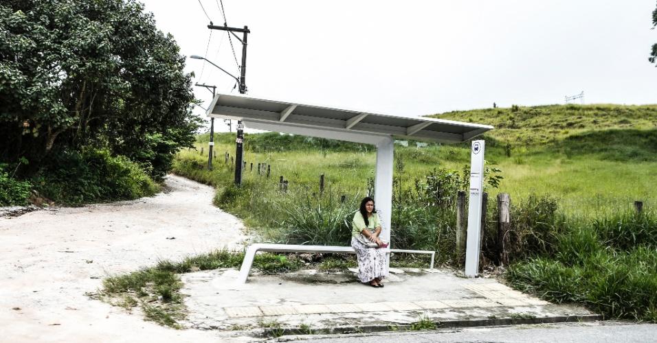 17.mar.2017 - Mulher espera pelo único ônibus que circula pela Ilha do Bororé, em um ponto instalado na via principal do bairro. Na lateral, uma das várias estradas de terra e cascalho que levam a sítios e chácaras