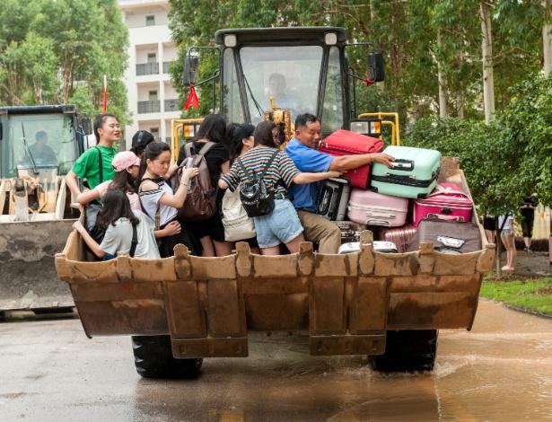 Trator leva estudantes em área inundada de faculdade em Guilin, província de Guangxi, na China