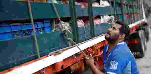 Humberto Aguilar amarra corda em seu caminhão carregado de vegetais para serem vendidos em Caracas - Carlos Garcia Rawlins/Reuters