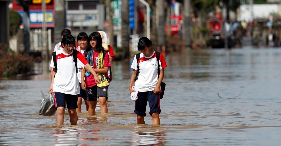 8.jul.2018 - Crianças caminham por área inundada na cidade de Kurashiki