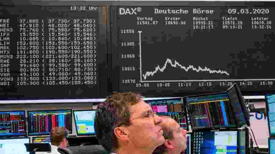 9.mar.2020 - Funcionários observam gráfico do índice de ações da Alemanha DAX, na bolsa de valores de Frankfurt  - Torsten Silz/AFP