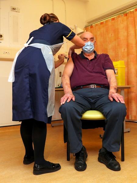 Brian Pinker, de 82 anos, é imunizado com vacina desenvolvida pela Oxford - Steve Parsons/Pool via REUTERS
