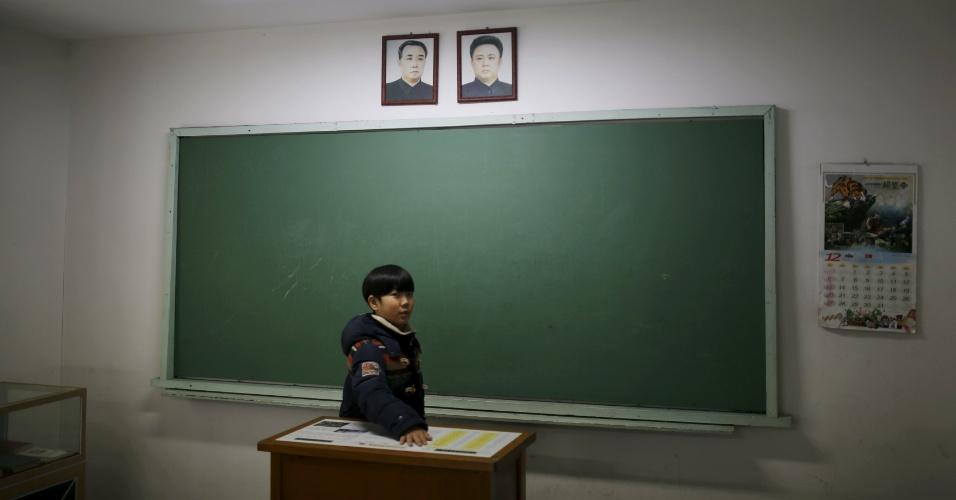 7.jan.2016 - Garoto observa a representação de uma sala de aula norte-coreana, que tem em uma das paredes os retratos do fundador da Coreia do Norte Kim Il Sung e do filho dele Kim Jong Il. O local fica na Plataforma de Observação Unificada, próximo a zona desmilitarizada que separa as duas Coreias, em Paju, na Coreia do Sul