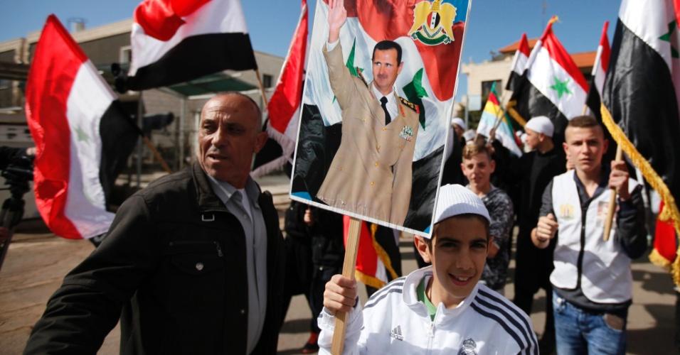 14.fev.2016 - Residentes drusos da aldeia Buqata nas Colinas de Golã, região anexada a Israel, acenam bandeiras da Síria e um cartaz do presidente sírio, Bashar al-Assad, durante um protesto contra a incorporação do território a Israel, em 1981