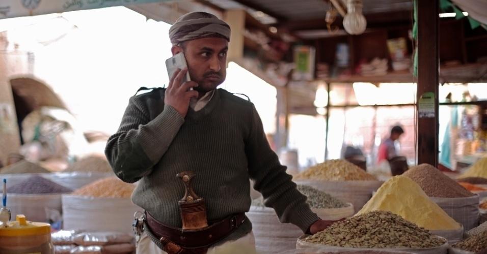 26.mar.2016 - Comerciante de especiarias conversa pelo celular no mercado do distrito antigo de Sanaa, capital do Iêmen. A imagem foi feita pela fotógrafa Rawan Shaif durante viagem por cidades das áreas controladas pelos houthis no norte do Iêmen, entre outubro de 2015 e fevereiro deste ano, para documentar os efeitos da guerra na população. Há exatamente um ano, tiveram início os bombardeios da coalizão árabe contra os houthis, que, segundo a ONU (Organização das Nações Unidas), mataram 3.218 civis e deixaram 5.778 pessoas feridas