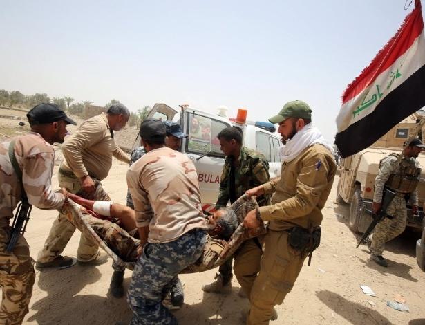 28.mai.2016 - Soldados das forças pró-governo no Iraque carregam homem ferido nos arredores de Fallujah durante operação para retomar o controle da cidade do EI