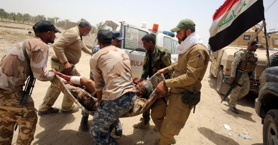 28.mai.2016 - Membros das forças pró-governo no Iraque carregam homem ferido nos arredores de Fallujah durante uma operação para tentar retomar o controle da cidade do Estado Islâmico, neste sábado. Centenas de pessoas deixaram a região após ataques simultâneos no Iraque e na Síria contra o grupo terrorista