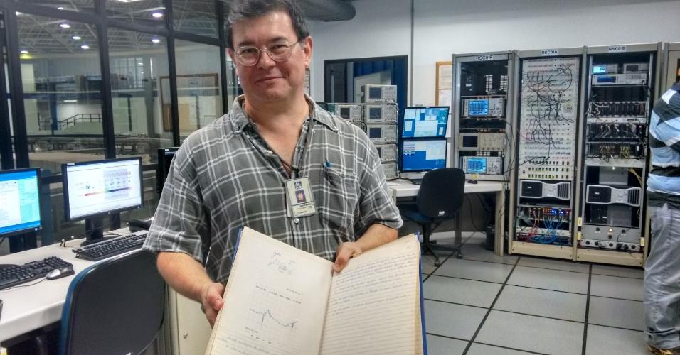 Ruy Farias, físico, responsável pela manutenção de aceleradores e sistemas de radiofrequência. Na imagem, ele segura o livro de registro da primeira volta de elétrons na fonte de luz síncrotron, que ocorreu no dia 22 de maio de 1996. Ruy estava presente