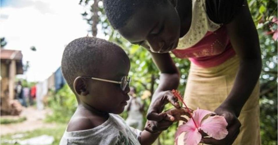 """8.jul.2016 - A prima de Criscent lhe explica o que é uma flor em frente à casa da família em Bundibugyo. """"Adquirir visão é um processo"""", disse Magyezi. """"Com os óculos, Criscent vai aprender a usar seus olhos e o que vê através deles. Assim poderá interpretar o mundo"""""""