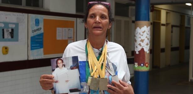 Mãe de Maria Eduarda exibe foto e medalhas da filha durante reconstituição em escola