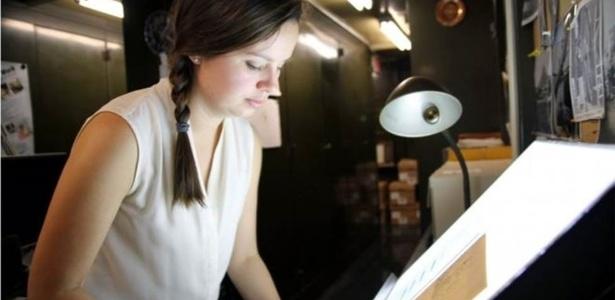 A curadora Lindsay Smith Zrull analisa uma antiga fotografia em chapa de vidro