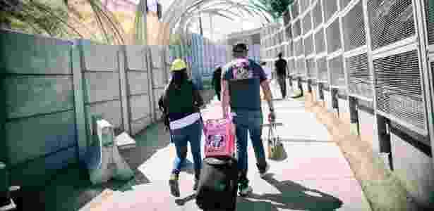 Pedestres caminham em direção ao portão de entrada para o México, na fronteira entre EUA e México, em San Ysidro, na Califórnia - SANDY HUFFAKER/NYT