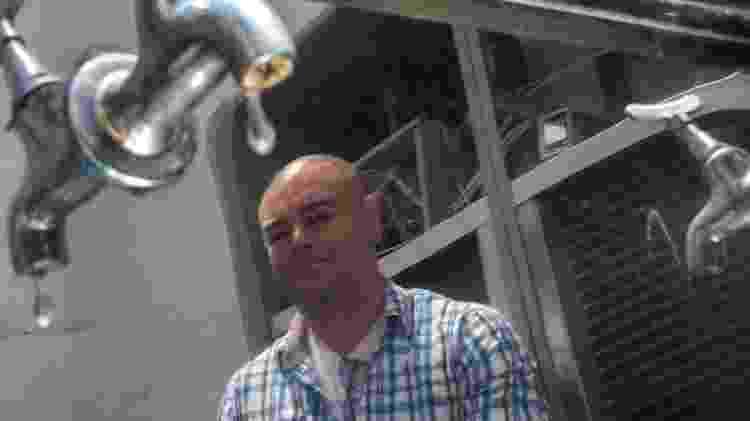 O engenheiro mecatrônico Pedro Ricardo Paulino, inventor de máquina que produz água potável extraída do ar ambiente, posa com uma das versões de sua máquina (9.out.2014) - Apu Gomes/Folhapress