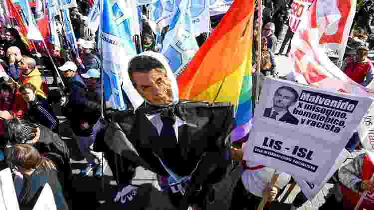 Manifestantes seguram boneco e cartazes contra a presença de Jair Bolsonaro em Santa Fé, na Argentina - Carolina Niklison/Reuters