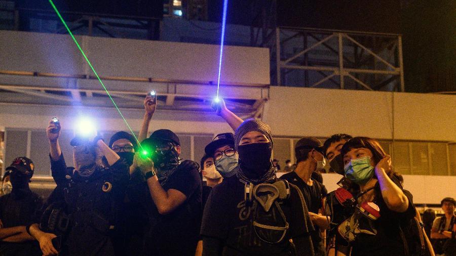 Manifestantes apontam raios laser para a polícia do lado de fora da estação de metrô Yuen Long durante um protesto em Hong Kong - Philip Fong/AFP