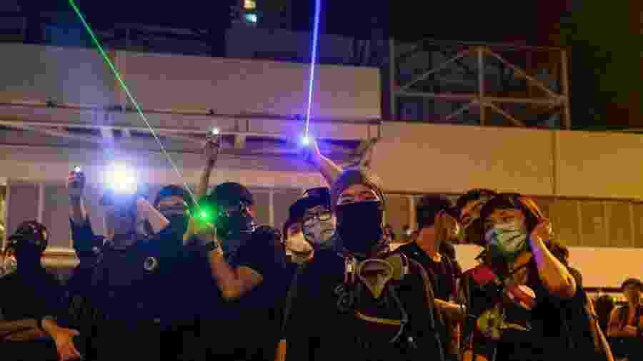 Manifestantes apontam raios laser para a polícia durante um protesto em Hong Kong - Philip Fong/AFP
