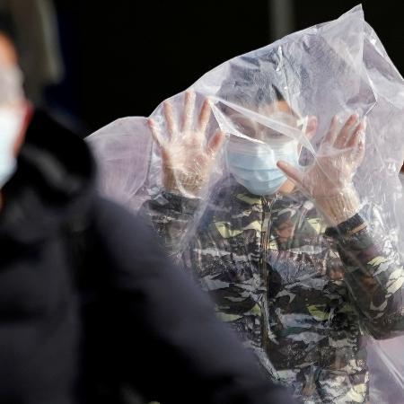 Homem caminha na estação de trem de Shangai, na China, coberto com uma sacola plástica em meio ao aumento de casos de covid-19 no país - ALY SONG/REUTERS