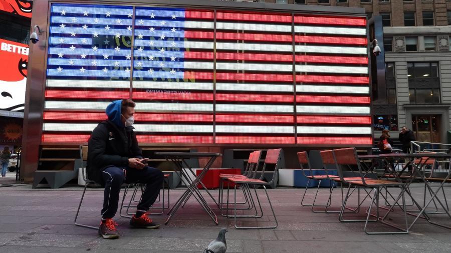 Homem usa máscara contra coronavírus na Times Square, em Nova York, em frente à bandeira dos Estados Unidos (EUA) - Gary Hershorn/Corbis via Getty Images