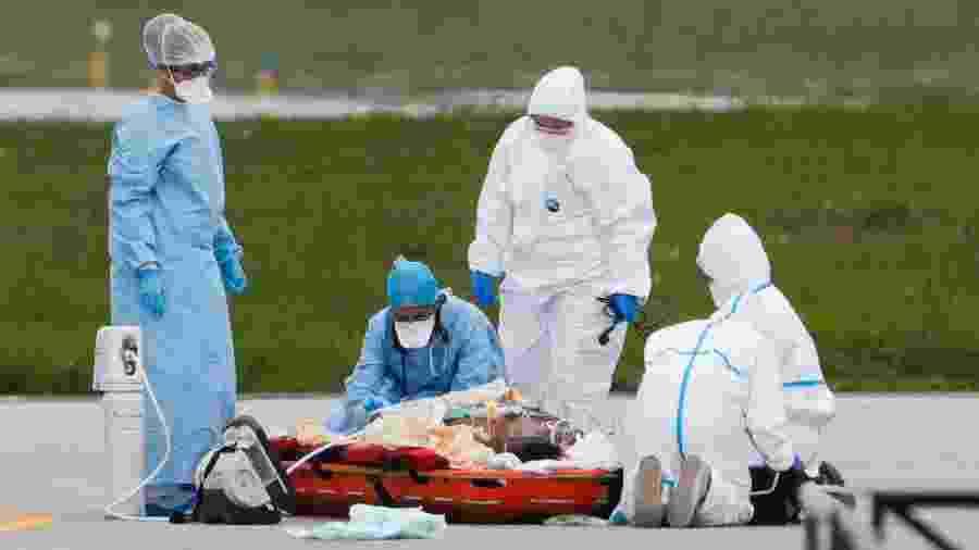 3.abr.2020 - Equipe médica prepara paciente infectado pelo novo coronavírus, no aeroporto de Orly, para transportá-lo de helicóptero até um hospital na região de Paris. Fechado para passageiros comuns, o aeroporto foi transformado em um ponto de liberação de pacientes para aliviar o atendimento em hospitais  - Geoffroy van der Hasselt/AFP