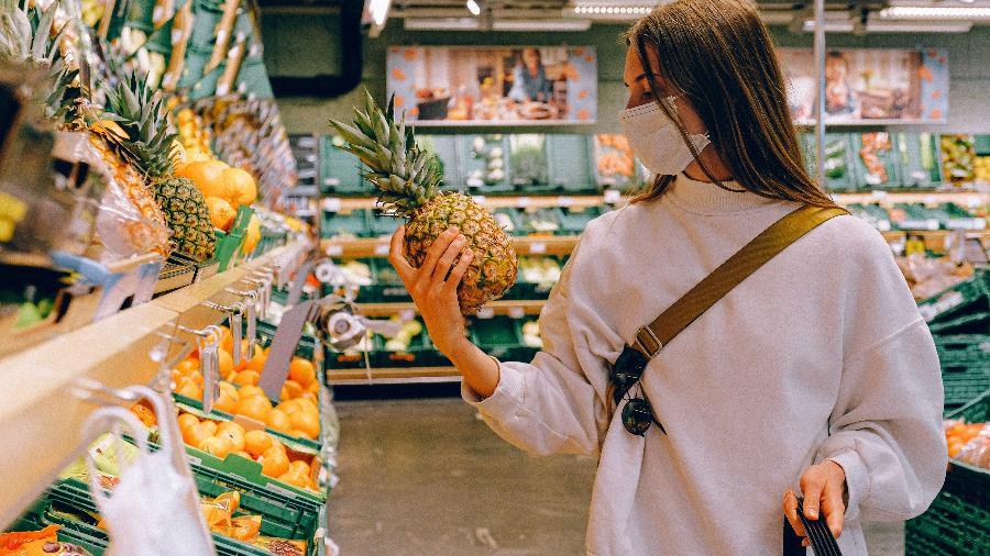consumidora olha abacaxi em um mercado supermercado compras - Anna Shvets/ Pexels