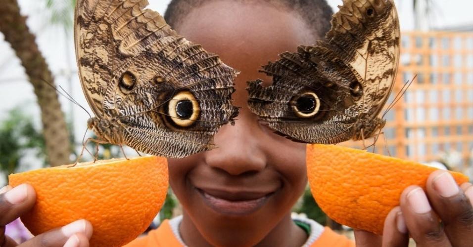 """23.mar.2016 - Bjorn, de 6 anos, posa para fotografia segurando laranjas com borboletas-coruja pousadas sobre elas no Museu de História Natural em Londres. Os desenhos das asas das borboletas parecem formar os olhos do menino. O museu londrino promove a exposição """"Sensational Butterflies"""" (borboletas sensacionais)"""