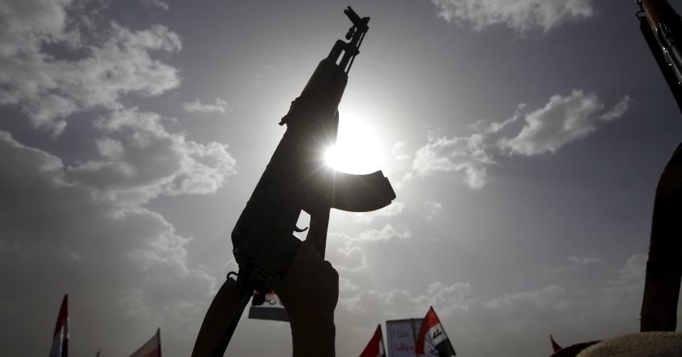 26.mar.2016 - Manifestante exibe arma durante protesto em Sanaa, capital do Iêmen. O ato com milhares de pessoas marca um ano dos ataques aéreos liderados pela Arábia Saudita. O Iêmen passa por uma intensa guerra civil e instabilidade política