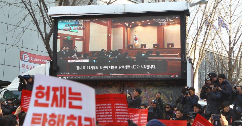 10.mar.2017 - Pessoas acompanham em telão, em Seul, a sessão dos juízes da Corte sul-americana que decidiu pelo impeachment da presidente Park Geun-hye