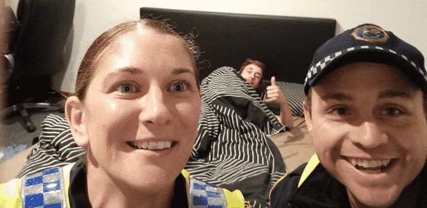 O estudante Reece Park estava deitado na sua cama fazendo um joinha com dois policiais sorridentes na sua frente - Reprodução/ Facebook/ Tasmania Police