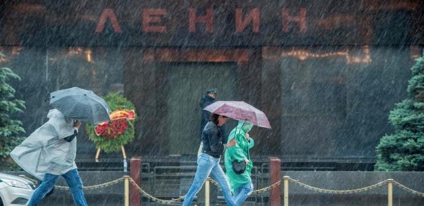 Pedestres protegem-se da chuva em Moscou: temporal deixou mortos e feridos na capital russa