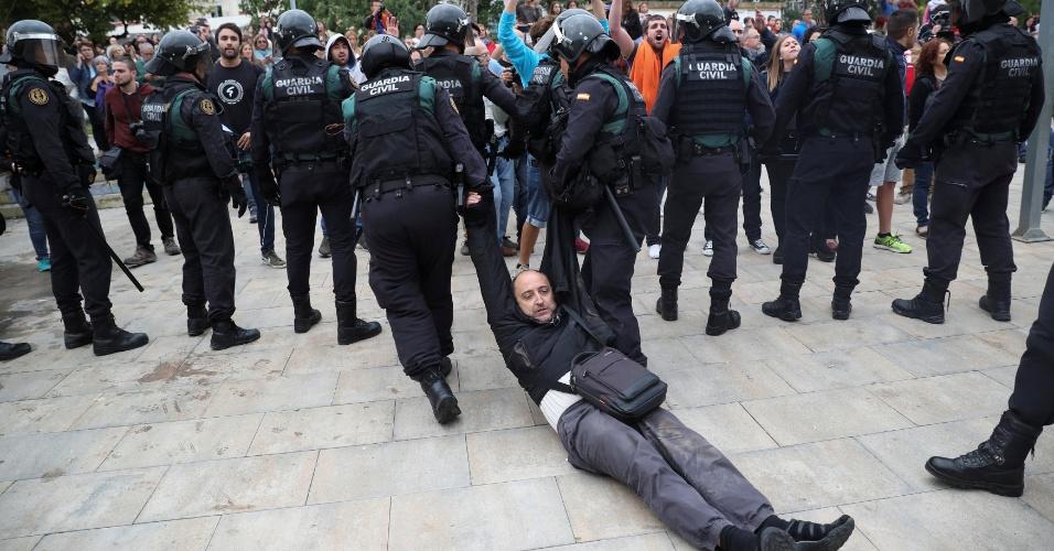 1.out.2017 - Homem é arrastado por oficiais da Guarda Civil Espanhola no município de Sant Julia de Ramis