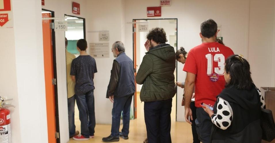 Eleitores na votação com camisa de partidos, em São Paulo