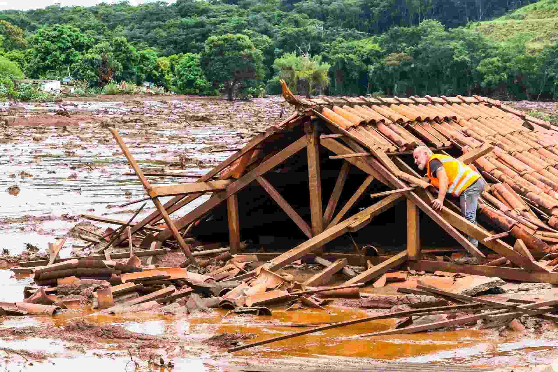 26.jan.2019 - Homem se equilibra em uma casa que foi engolida pela lama da barragem 1 da Mina do Feijão, em Brumadinho - CADU ROLIM/FOTOARENA/ESTADÃO CONTEÚDO