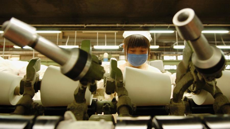 Jovem trabalha na indústria têxtil, em Pequim, em imagem de 2007 - Marcel Crozet / International Labour Organization